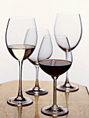 A Glass of Red and a Glass of White Wine with Two Empty Glasses