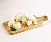 Assorted Soft Cheeses on a Wooden Board