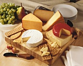 Cheese and crackers on a wooden board with fresh fruit