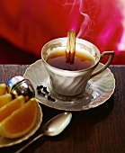 A Cup of Tea with Cloves, a Cinnamon Stick and Lemon Wedges