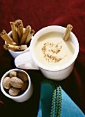 A cup of hot vanilla with nutmeg and a cinnamon stick