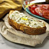 Olive Oil Pouring onto a Slice of Crusty Bread Topped with Goat Cheese