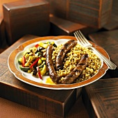 Serving of Merguez Sausage Over Israeli Couscous Served with Vegetable Medley