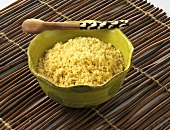 Couscous Served in a Green Bowl with Wooden Spoon on Bamboo Mat