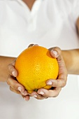 Close Up of Female Hands Holding a Whole Orange