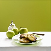 Slices of Baked Apple on a Plate with Fresh Whole Apples