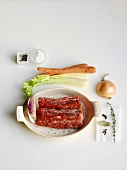 Raw Beef Roast in a Baking Dish with Raw Vegetables and Spices
