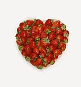 Overhead of Fresh Strawberries in White Heart Shaped Bowl; White Background