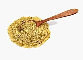 Pile of Mustard Seeds with Wooden Spoon on White Background