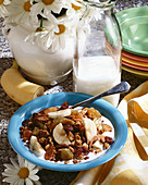 Bowl of Granola Cereal with Dried Fruit and Banana Slices; Milk and Flowers
