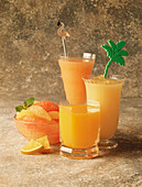 Three Assorted Glasses of Citrus Juice; Bowl of Grapefruit Slices and Orange Wedges