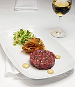 Serving of Steak Tartar with Mixed Greens on a White Plate