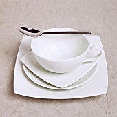 Single Place Serving With Square and Round White Dishes and a Spoon