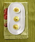 Overhead of Three Deviled Eggs on a White Oval Platter