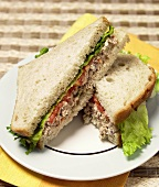 Tuna Salad Sandwich with Tomato and Lettuce Sliced in Half on White Plate