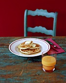Plate of Pancakes with Butter and Maple Syrup on Table with Glass of Orange Juice