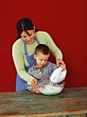 Woman and boy making pastry with electric mixer