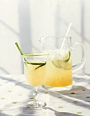 Glass of Limeade with Green Stirrer and Lime Slice; Pitcher of Limeade