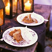 Plates of Steamed Indian Pudding with Whipped Cream on Outdoor Table; Lanterns