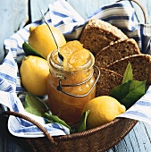 Jar of Lemon Marmalade with Fresh Lemons and Sliced Bread in a Basket