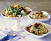 Spaghetti with Tomatoes and Pesto in Bowls with Green Bean and Tomato Salad in Serving Bowl