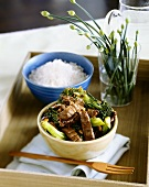 Bowl of Beef and Broccoli Stir Fry; Bowl of White Rice; Wooden Fork on Tray