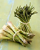 Two Fresh Bundles of Asparagus Tied with String; One with Thin Spears and One with Thick Spears