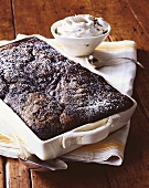 Chocolate Pudding Cake Topped with Powdered Sugar in Baking Dish; Bowl of Whipped Cream