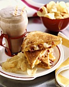 Cheddar and Swiss Grilled Cheese with Bacon on a Plate with Chips and a Chocolate Shake