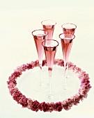 Rosé-Champagner in Champagnerflöten und rosa Blumenkranz