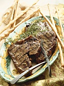 Steak Grilled with Garlic and Rosemary on a Platter with Breadsticks
