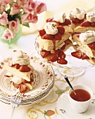 Strawberry Shortcakes on a Cake Plate and One on a Dish; Cup of Tea