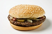 A Hamburger with Pickles, Onions and Ketchup on a Sesame Seed Bun