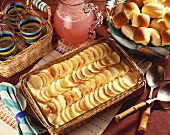 Scalloped Potatoes in Baking Dish on Picnic Table with Basket of Rolls and Pitcher of Pink Lemonade
