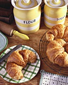 Fresh Croissants; One on a Plate with Others on Wire Platter; Flour and Sugar Canisters