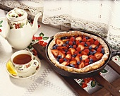 Strawberry and Blueberry Plantation Skillet Cake in Skillet; Cup and Pot of Tea