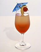 Cocktail in a Stem Glass with Blue Cocktail Umbrella and Lime and Cherry Garnish on White Background