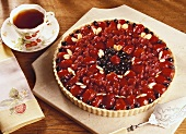 Berry Tart Made with Strawberries, Raspberries and Blueberries with Almonds; Cup of Tea
