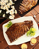 Grilled Barbecued Ribs on a White Platter and on Grill