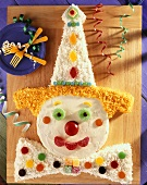 Overhead of Clown Cake for Childs Birthday Party on Wooden Cutting Board