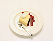 Piece of Poundcake with Whipped Cream and Raspberry Sauce on a White Plate with Fork