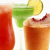 Three frozen cocktails garnished with fruit (close-up)