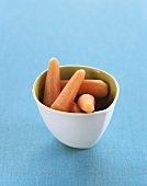 Peeled Baby Carrots in a White Bowl on a Blue Background