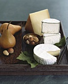 Assorted Cheeses (Brie, Humbolt Fog Goat Cheese & Grevere) with Nuts and Pears on a Rustic Wooden Tray