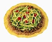 Tostada with beef, bean puree, lettuce, tomatoes & cheese