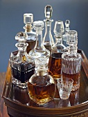 Assorted Decanters Filled with Assorted Liquors on a Glass Top Table