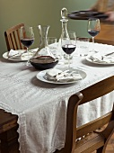 Woman bringing tray to a laid table with red wine & decanter