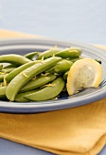 Sugar Snap Peas with Lemon Zest and Lemon Slice on Blue Plate
