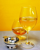 Glass of white wine and cognac with small silver bowl