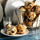 Blueberry Muffins in a Wire Basket and on a Plate with a Glass of Milk